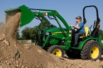 Woman driving a 2032R Compact Utility Tractor with mowing attachment