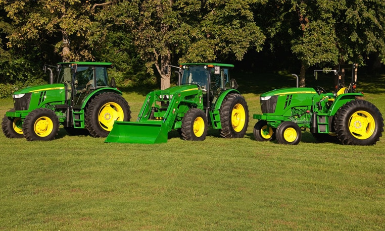 Three 6D Series Utility Tractors displayed in a grass field.