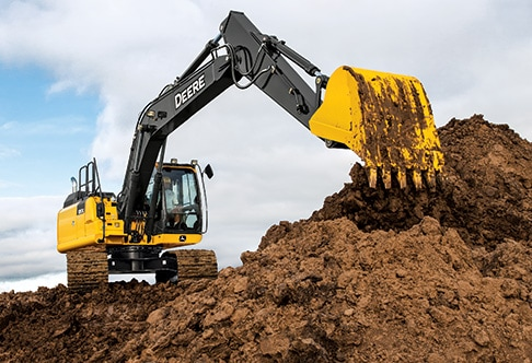 Front view of a 180G LC Excavator digging on hillside