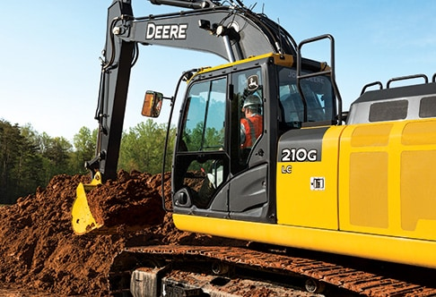 Rear three quarter view of 210G LC Excavator digging dirt