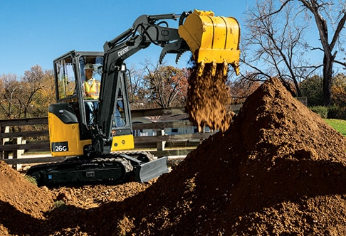 Right hand side view of a 26G compact excavator filling in a ditch