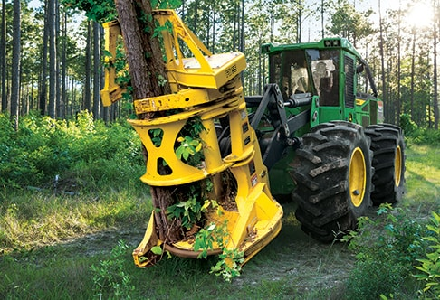 Front view of the 843L Wheel Feller Buncher sawing into a tree in the forest