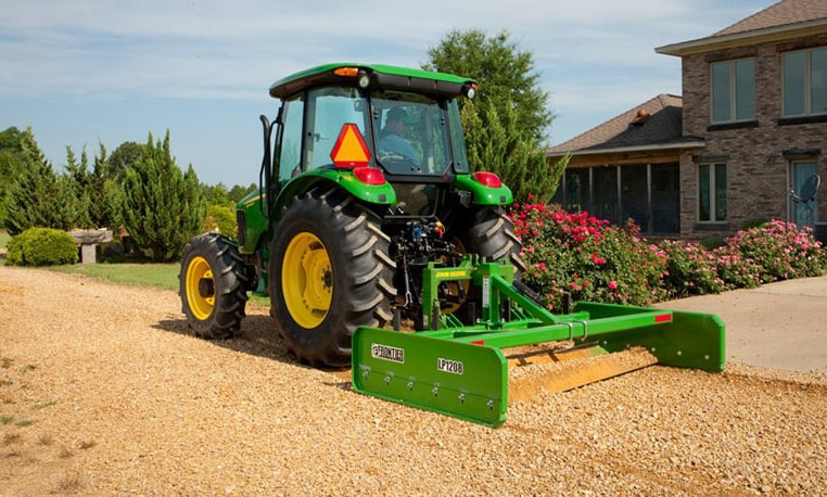 John Deere tractor with land plane attachment smoothing gravel in a driveway