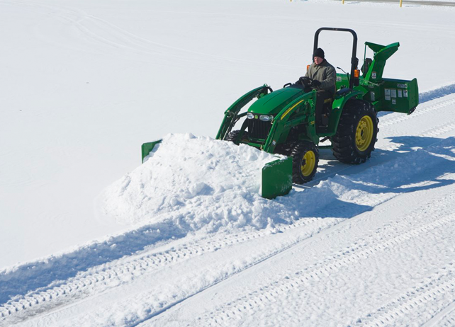 Overhead view of a John Deere tractor using a AS10H Series Snow Push to clear snow