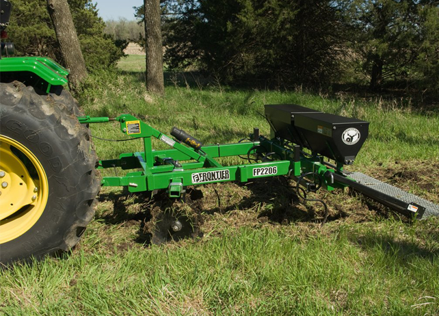 FP22 Series Food-Plot Seeder working in a grassy field near a group of trees