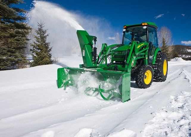 John Deere tractor using a SB21 Series Loader-Mount Snow Blower to clear snow