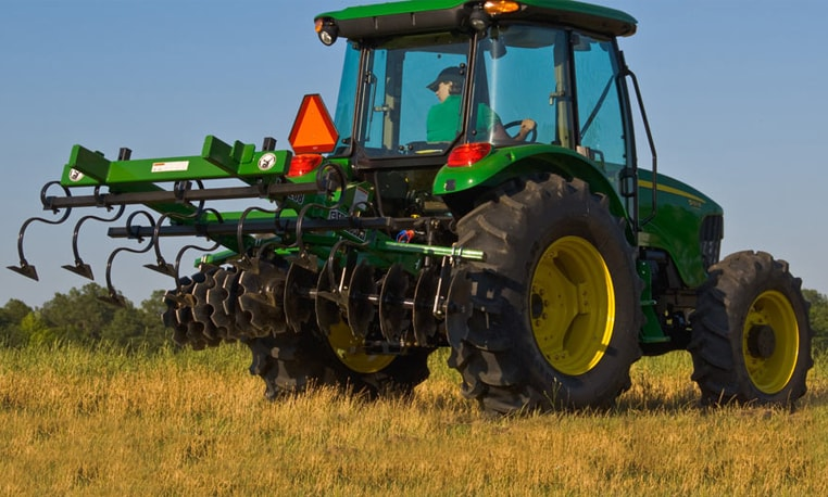 Rear view of a John Deere tractor with a Mulch Finisher in a field
