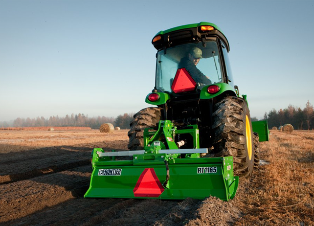 Rear view of a man driving a John Deere tractor with RT11 Series Rotary Tiller