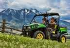 Two passengers are driving a green and yellow Gator 550 in the mountains.