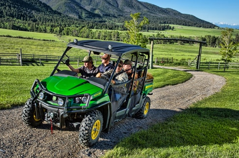 Four passengers are driving a green and yellow Gator 550 S4 on a pathway through the valley.