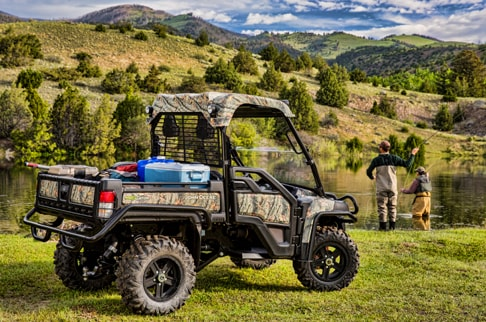 A camo Gator 825i's cargo space is packed with fishing equipment while two men are fishing.