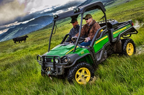 Two passengers are driving a green and yellow Gator 825i through a cattle field.