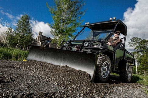 Olive XUV 825i with a front attachment is pushing dirt in front of a residence.