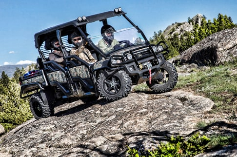 Four passengers are climbing rocks in a camo 825i S4.
