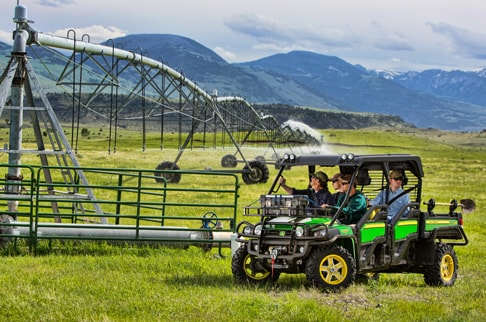 Four passengers parked in a green and yellow Gator 825i S4 with attachments are observing sprayers in a field.