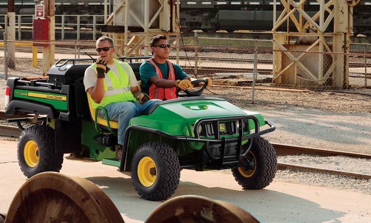 Two men driving a TX Gator around a railroad yard.