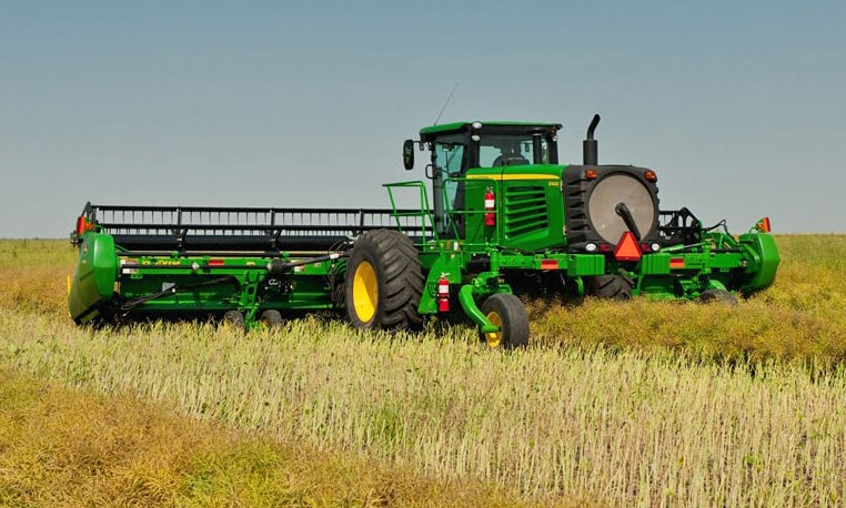 Rear view of a John Deere Self-Propelled Windrower harvesting a field