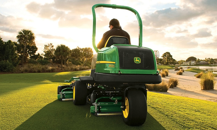 Man operates a Riding Greens Mower on the tee of a golf course