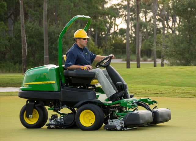 Worker uses 2500B Diesel mower to mow golf course green