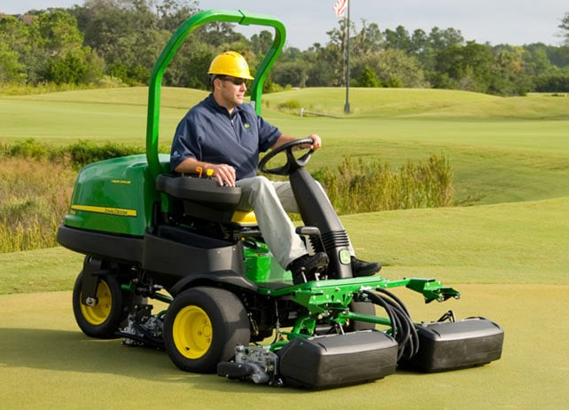 Worker uses 2500B Gas mower to mow golf cours green