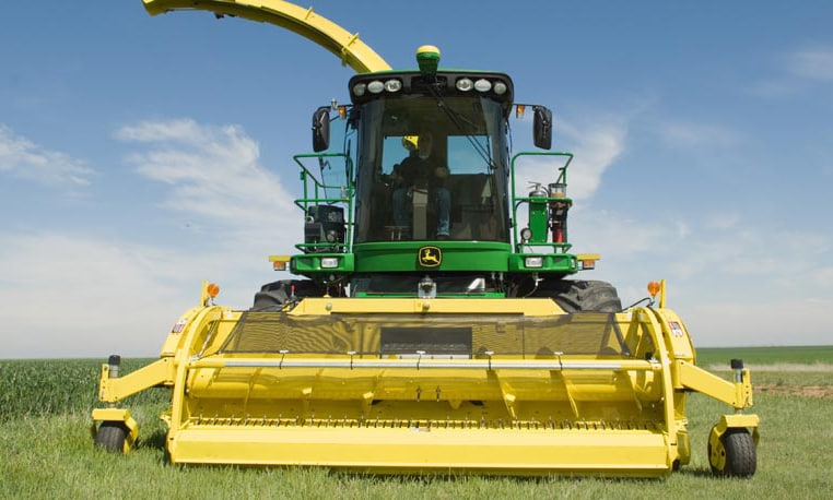 Front view of a John Deere Forage Harvester with SPFH Hay Pickup attachment working in a field