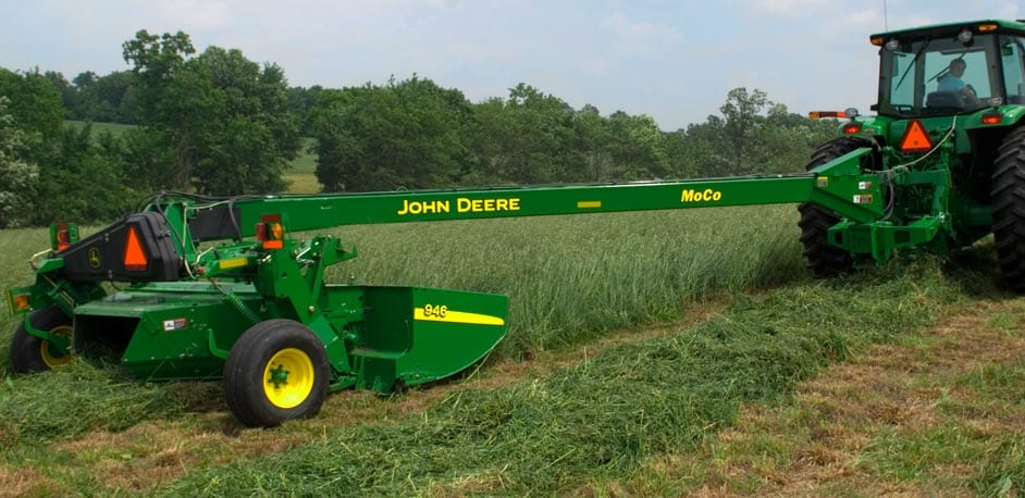 John Deere tractor pulling a 900 Series Mower-Conditioner in a field with trees in the background