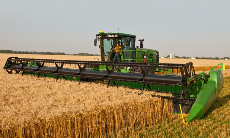 John Deere Self-Propelled Windrower with 600D Draper Platform harvesting corn in a field