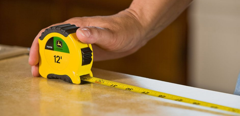 closeup of a hand using a John Deere tape measure to measure a piece of wood