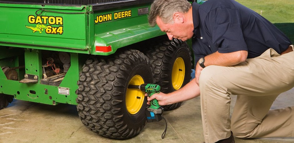 man kneeling down to fix a John Deere Gator tire with a John Deere power tool