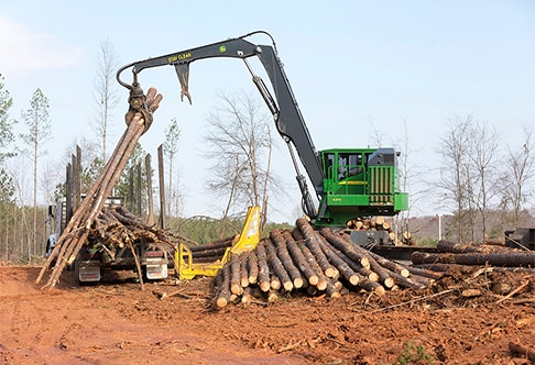 Right hand view of 437E Knuckleboom Loader delimbing logs