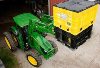 John Deere Utility Tractor using a pallet fork to lift and haul a load