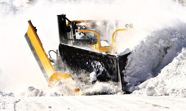John Deere motor grader plowing through a large pile of snow