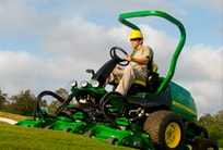 Worker using a PrecisionCut mower to trim grass on a golf course