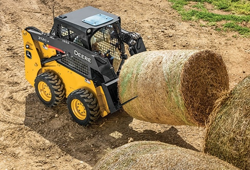 Overhead view of a 312GR Skid Steer with AF66 ag fork attachment lifting a round hay bale onto a trailer