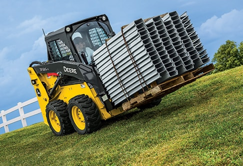 Right hand view of a 312GR Skid Steer with rail style pallet fork attachment transporting a pallet of vinyl sheet piling sections