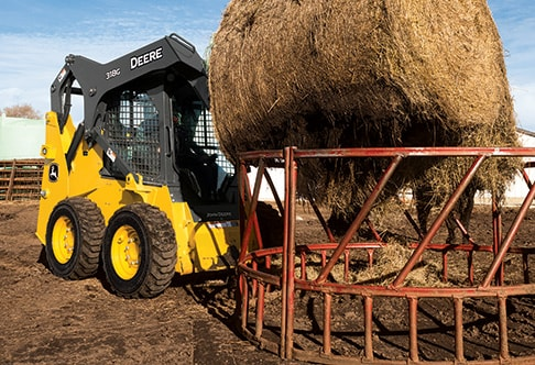 Right hand view of a 318G Skid Steer with a round bale spear attachment placing round bale of hay in a bale feeder