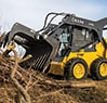 Left hand view of a 318G Skid Steer with a GT72 brush tined grapple attachment gathering up fallen tree branches