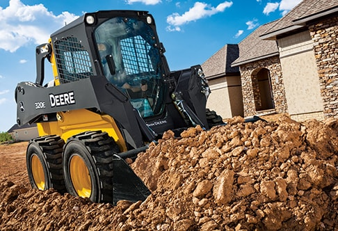 320E Skid Steer loading bucket of dirt