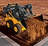 320E Skid Steer dumping bucket of dirt