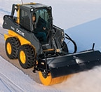 Skid steer using a broom attachment to sweep snow off sidewalk