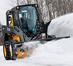 Skid steer using snow blower attachment to remove snow from a driveway