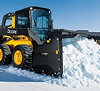 Skid steer using a snow pusher attachment