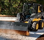 Skid steer using broom attachment to sweep leaves off sidewalk