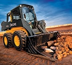 Skid steer using rock bucket attachment to remove rocks\