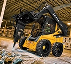 Skid steer using breaker attachment to bust up concrete