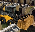 Skid steer using grapple attachment to transport a square hay bale