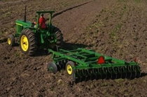 John Deere tractor with tillage equipment working in a field