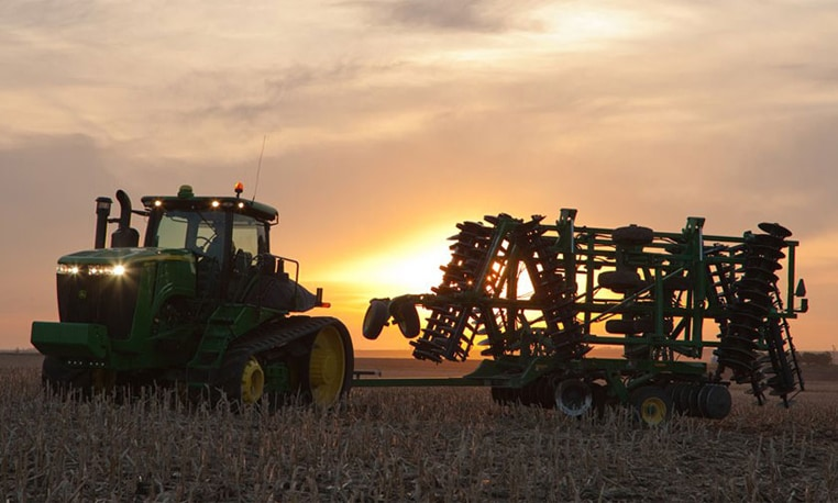 John Deere tractor with tillage equipment in a field with sunset in the background