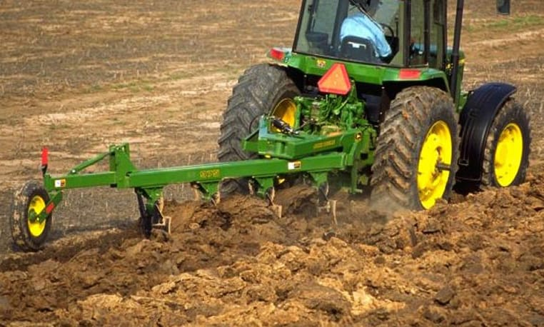 Moldboard Plow attached to John Deere tractor working up a field