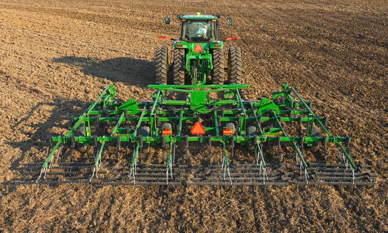 Rear view of a John Deere tractor with seedbed tillage equipment in a field